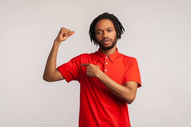 Mężczyzna podnoszący rękę wskazującą na biceps wyrażający siłę