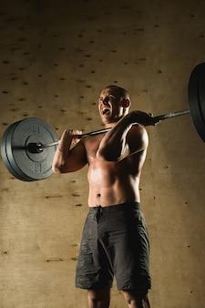 Mężczyzna podnoszenia ciężarów. trening mięśni człowieka w siłowni, ćwiczenia ze sztangą