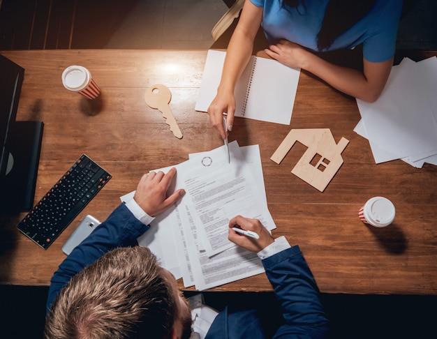 Mężczyzna podpisać polisę ubezpieczeniową domu na kredyty mieszkaniowe. agent nieruchomości z klientem przed podpisaniem umowy.