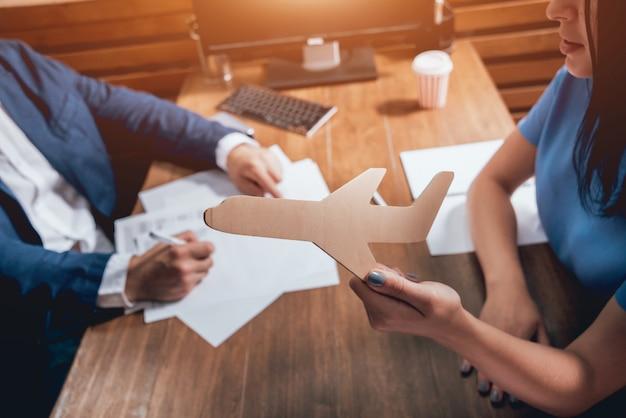 Mężczyzna podpisując polisę ubezpieczeniową na życie, agent trzyma drewniany model samolotu.