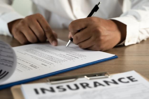 Mężczyzna podpisujący polisę ubezpieczeniową