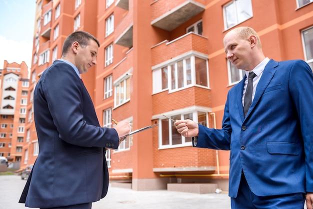 Mężczyzna podpisujący umowę kupna mieszkania naprzeciw nowego budynku
