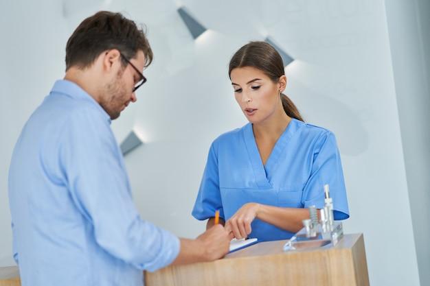 Mężczyzna podpisuje dokumenty w klinice dentystycznej