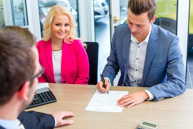 Mężczyzna podpisuje sprzedaż kontrakt dla samochodu przy przedstawicielstwem firmy samochodowej