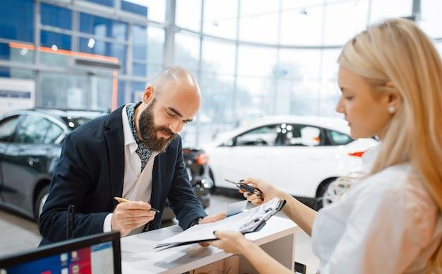 Mężczyzna podpisuje umowę kupna nowego samochodu w salonie samochodowym. klient i sprzedawczyni w salonie samochodowym, mężczyzna kupujący transport, firma dealera samochodowego