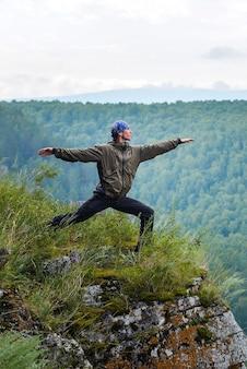 Mężczyzna podróżnik ćwiczący jogę wojownika na klifie góry