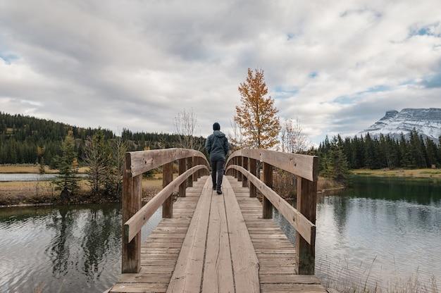 Mężczyzna podróżnik idący przez drewniany most jesienią w cascade ponds, park narodowy banff, kanada