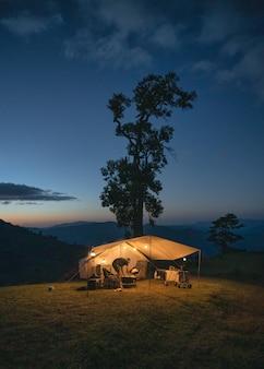 Mężczyzna podróżnik kemping w żółtym namiocie z dużym drzewem na wzgórzu na wsi o zmierzchu