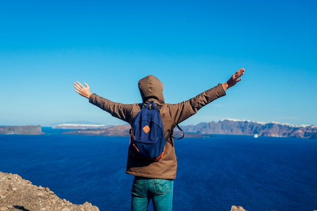 Mężczyzna podróżnik podniósł ręce czując się swobodnie i szczęśliwy na wyspie santorini jesienią. turysta podziwiający widok na kalderę