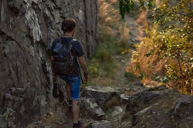 Mężczyzna podróżnik spaceruje w pobliżu skał i jesiennego lasu trzyma w dłoni ukulele wysokiej jakości zdjęcie