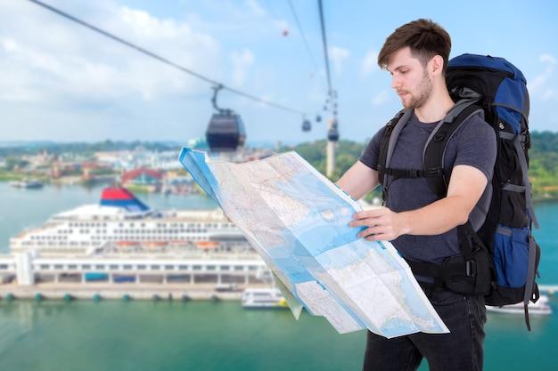 Mężczyzna podróżnik szukający właściwego kierunku na mapie, wolności i koncepcji aktywnego stylu życia