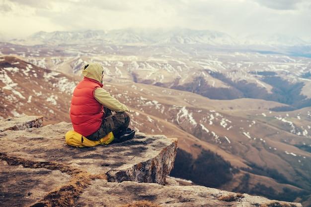 Mężczyzna podróżnik w czerwonej kurtce siedzi na skraju urwiska, na żółtym plecaku, cieszy się naturą