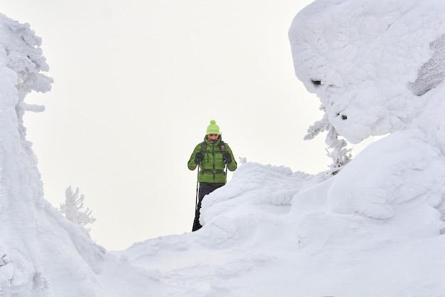 Mężczyzna podróżnik w zimowych górach wśród ośnieżonych klifów podczas zamieci śnieżnej