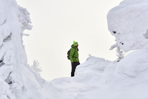 Mężczyzna podróżnik w zimowych górach wśród ośnieżonych klifów