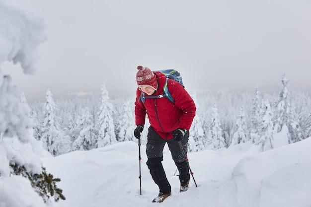 Mężczyzna podróżnik wspina się na górę zimą podczas opadów śniegu