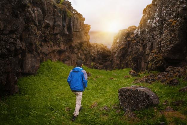 Mężczyzna podróżnik wycieczkuje przez islandia krajobraz.