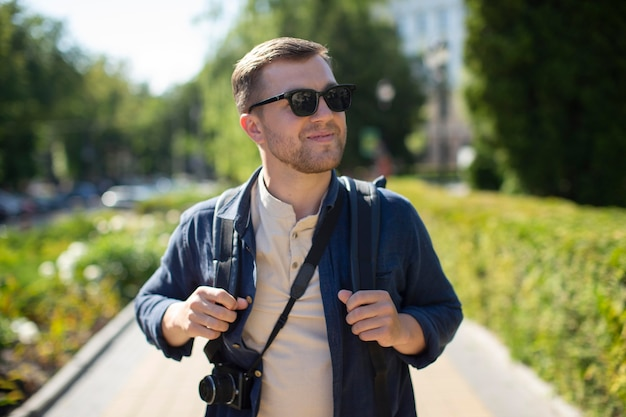 Mężczyzna podróżnik z aparatem w lokalnym parku