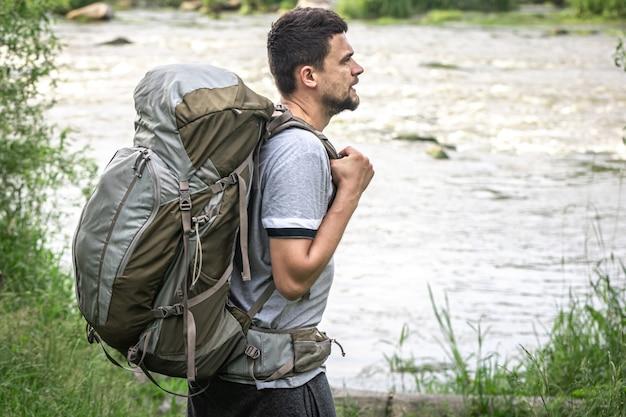 Mężczyzna podróżnik z dużym plecakiem turystycznym w pobliżu rzeki.