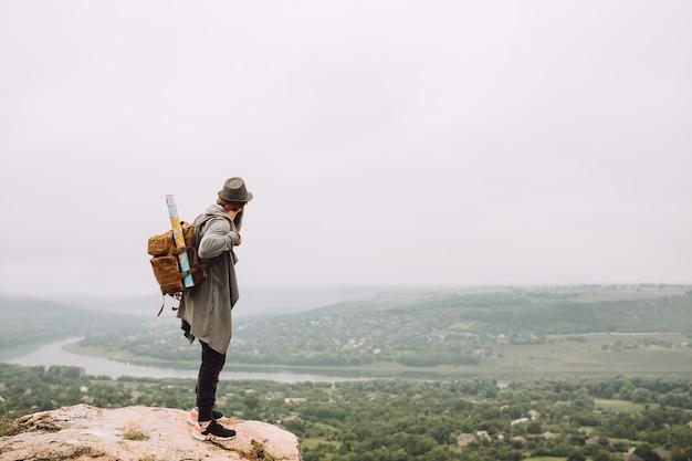 Mężczyzna podróżnik z plecakiem i mapą.