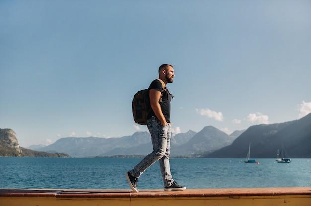 Mężczyzna podróżnik z plecakiem na tle alpejskich gór i jezior