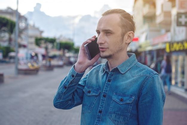 Mężczyzna podróżnik z plecakiem rozmawia przez telefon na ulicy.