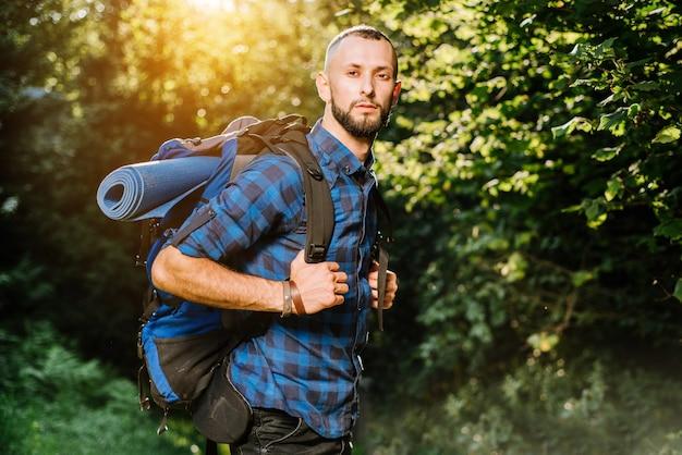 Mężczyzna podróżnik z plecakiem w drewnie