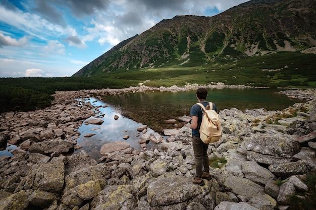 Mężczyzna podróżnik z plecakiem w pobliżu górskiego jeziora