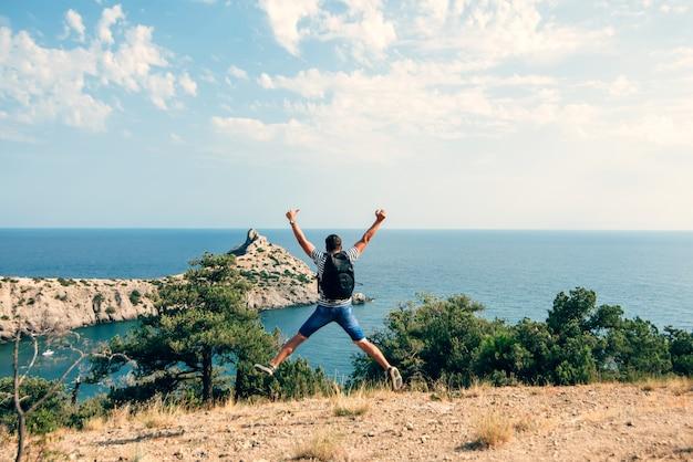 Mężczyzna podróżnik z radością i radością skacze z plecakiem