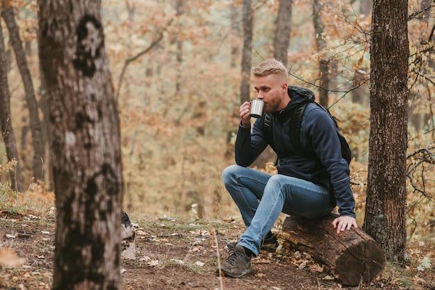 Mężczyzna podróżujący po jesiennym lesie zatrzymuje się i pije herbatę.