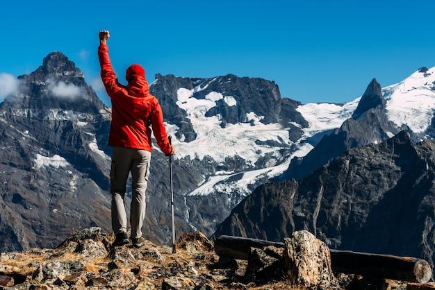 Mężczyzna podróżujący po kaukazie. sporty górskie. sportowiec szczęśliwy finisz. turystyka górska. piesza wycieczka. podróż w góry. nordic walking wśród gór. skopiuj miejsce