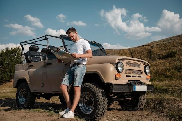 Mężczyzna podróżujący samochodem i patrząc na mapę