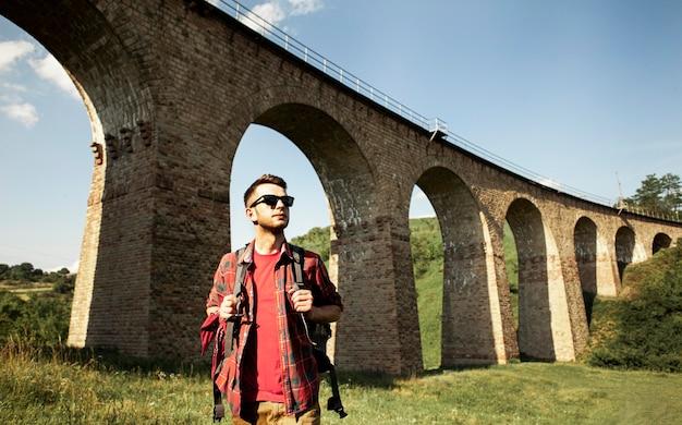 Mężczyzna podróżujący samotnie obok mostu
