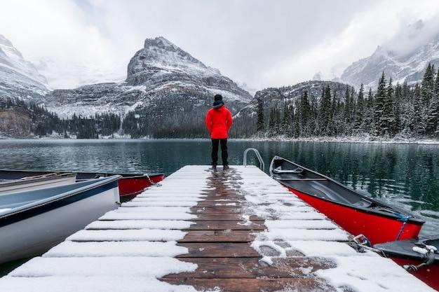 Mężczyzna podróżujący stojący na drewnianym molo z czerwonym kajakiem i śniegiem w lake o'hara w parku narodowym yoho
