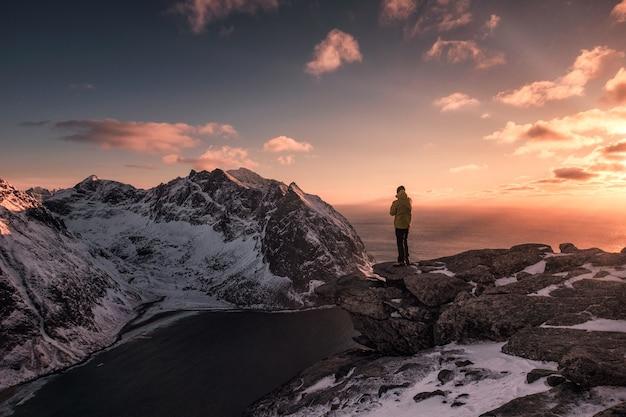 Mężczyzna podróżujący stojący na szczycie góry ryten o zachodzie słońca w norwegii