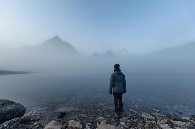 Mężczyzna podróżujący stojący nad jeziorem magog z mount assiniboine w mglistym parku prowincjonalnym