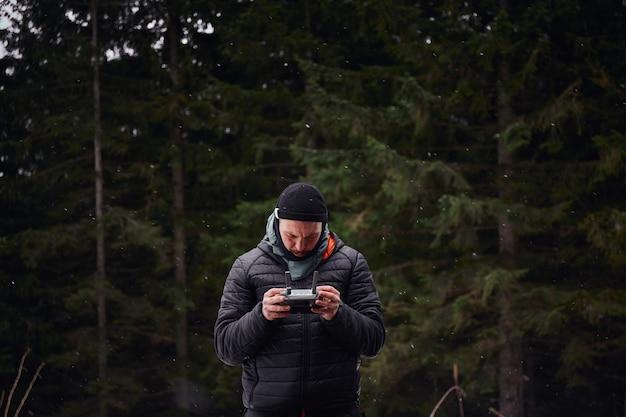 Mężczyzna podróżujący stojący w lesie i latający z dronem