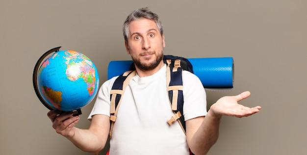 Mężczyzna podróżujący w średnim wieku z mapą kuli ziemskiej