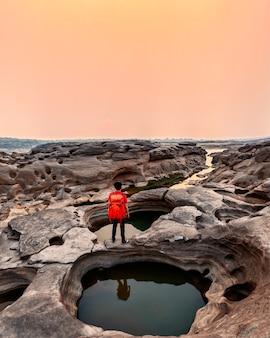 Mężczyzna podróżujący z plecakiem stojący na otworach skalnych wielkiego kanionu o zachodzie słońca w sam phan bok