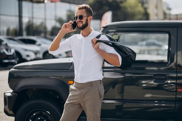Mężczyzna podróżujący z torbą i stojący przy samochodzie