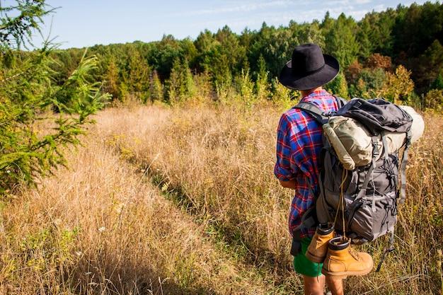 Mężczyzna podróżuje w polu z kapeluszem