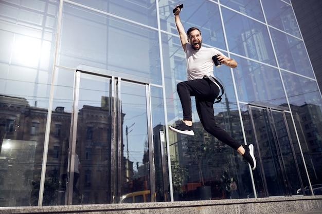 Mężczyzna podskakujący na ulicy ze smartfonem