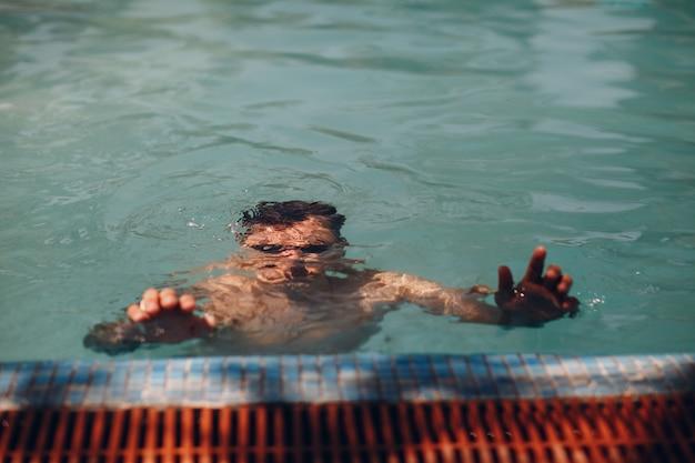 Mężczyzna podwodny w basenie z błękitne wody