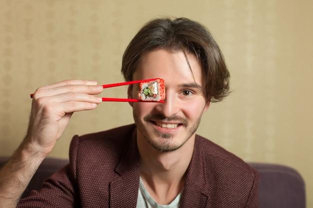 Mężczyzna pokaż pałeczki z rolką sushi.