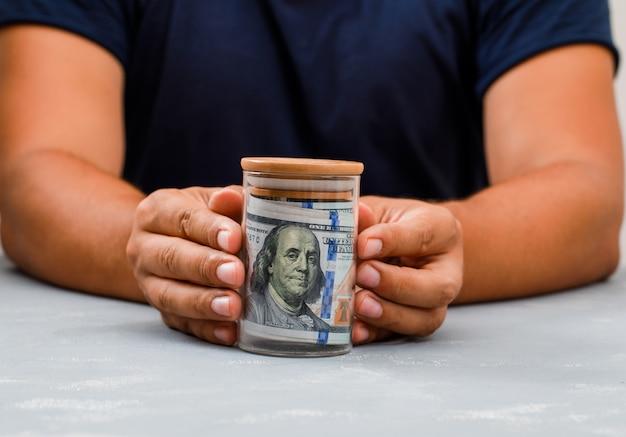 Mężczyzna pokazano słoik pieniędzy.