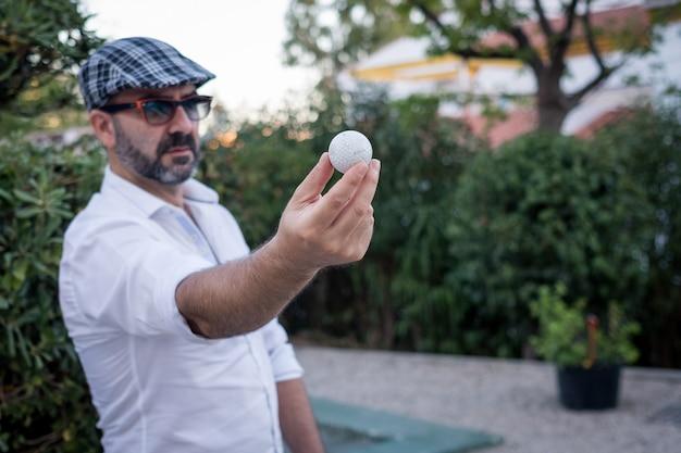 Mężczyzna pokazując piłeczkę golfową w dłoniach