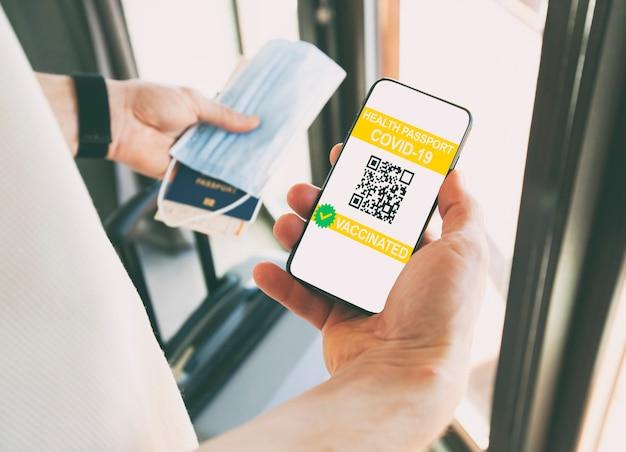 Mężczyzna pokazujący aplikację paszportu zdrowia cyfrowego w telefonie komórkowym do podróży.