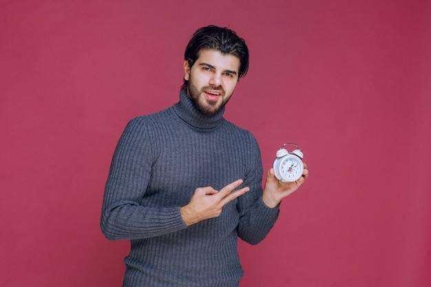 Mężczyzna pokazujący biały budzik i punkt pakowania najlepszej oferty.