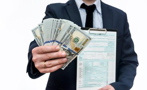 Mężczyzna pokazujący formularz podatkowy 1040 i dolary w fan