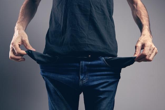 Mężczyzna pokazujący puste kieszenie na szarym tle
