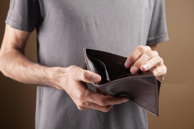 Mężczyzna pokazujący pusty portfel na brązowym tle